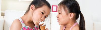 a girl sharing her ice cream with her younger sister